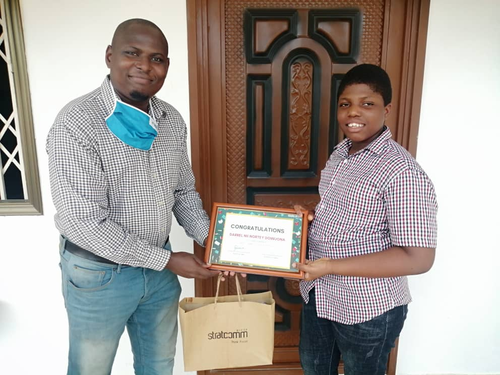 Media and Stakeholder Relations Lead at Stratcomm Africa Bernard Allotey (L) presenting the prize to the winner of the aged 12 category Master Darrel Nortey Dowuona